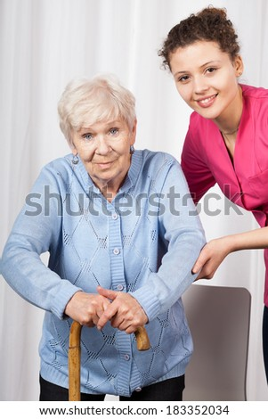 Nurse with elderly woman walking on crutches