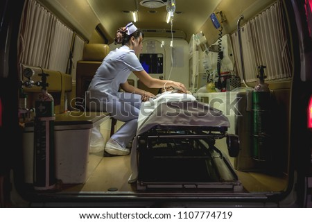 Nurse with patient. Young chinese nurse with her emergency patient in ambulence taking care of her patient. Real ambulence in hospital. Medical concept.