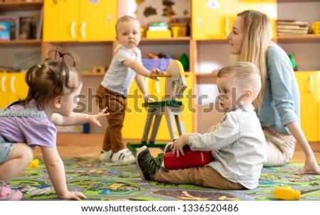 Nursery babies with mentor playing in kindergarten