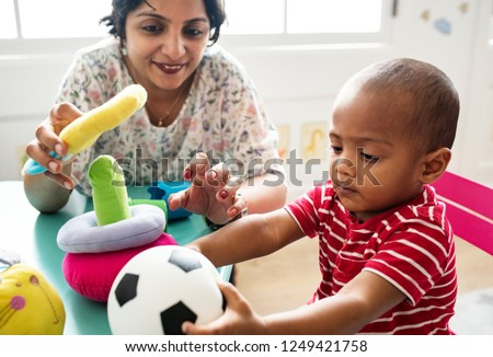 Nursery child playing with teacher in the classroom