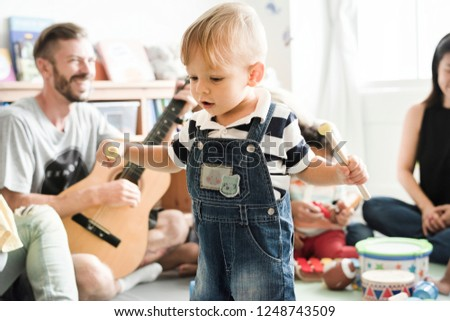 Nursery children playing with musical instruments in the classroom