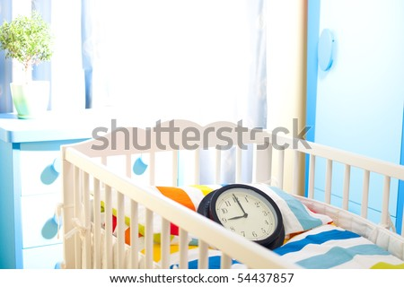 Nursery room with baby bed and clock counting time for new owner