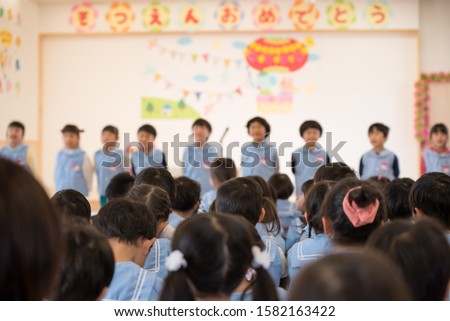 Nursery school children looking at graduate students ストックフォト ©