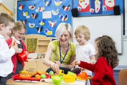 Nursery teacher playing kitchen role play with her students in the classroom.