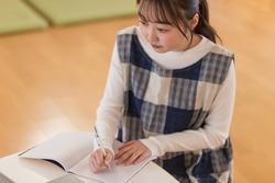 Nursery teacher writing a diary