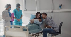 Nurses bringing newborn to young happy couple in hospital. Medical workers in safety mask giving baby to young mother lying in hospital bed after giving birth
