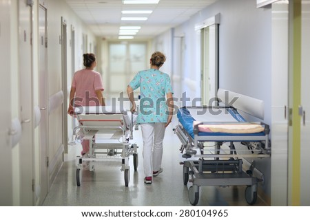 Nurses pushing a mobile bed in a hospital corridor
