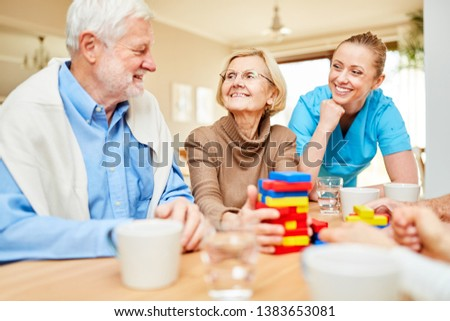 Nursing care takes care of demented senior citizens playing with building blocks