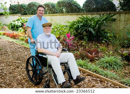 Nursing home orderly takes a senior man for a walk in the garden.