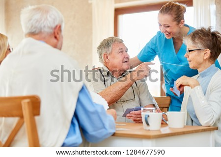 Nursing lady has fun with a group of seniors playing cards in the nursing home