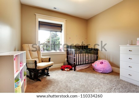 Nursing room for baby girl with brown wood crib and beige walls. #110334260