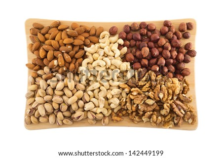 Nut mix of peanut, hazelnut, walnut, almond and pistachio over the wooden cutting board isolated over white background