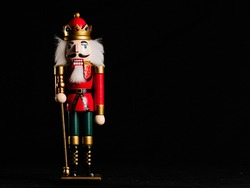 NUTCRACKER DOLL ON BLACK BACKGROUND AND COPY SPACE ON THE RIGHT
