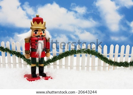 Nutcracker sitting on snow with white fence and green garland on a sky background