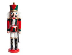 Nutcracker wooden doll wearing an old Military style uniform. A traditional figurine of Christmas time over white background.