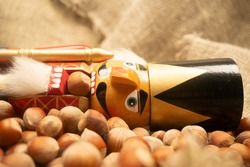 Nutcracker wooden figure of a soldier for cracking nuts on the background of scattered nuts. Traditional symbol of Christmas and New Year. Close up.
