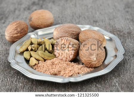 Nutmeg and cardamom on a white background