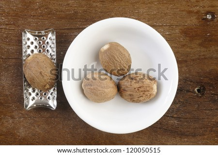 nutmeg and grater on  wooden table background
