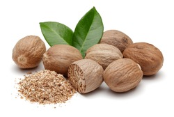 Nutmeg granules and nutmegs with leaves isolated on white background