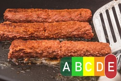 nutri score food labeling. oily frying pan with sausages - cevapcici. fatty foods have an E Red Nutri score