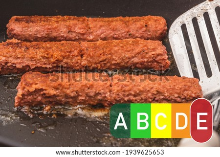 nutri score food labeling. oily frying pan with sausages - cevapcici. fatty foods have an E Red Nutri score Foto stock ©