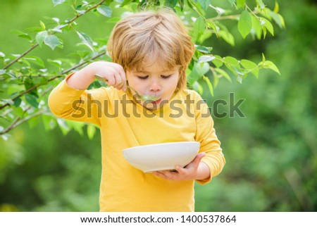 Nutrition for kids. Little toddler boy eat porridge outdoors. Having great appetite. Organic nutrition. Healthy nutrition concept. Nutrition habits. Kid hold spoon. Small child enjoy homemade meal. #1400537864