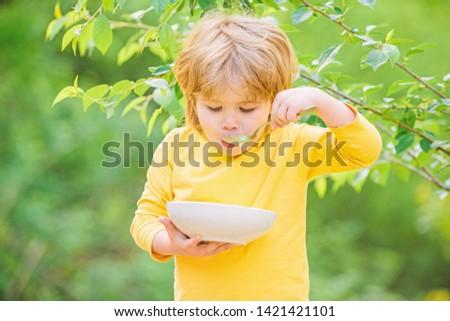 Nutrition for kids. Little toddler boy eat porridge outdoors. Having great appetite. Organic nutrition. Healthy nutrition concept. Nutrition habits. Kid hold spoon. Small child enjoy homemade meal.