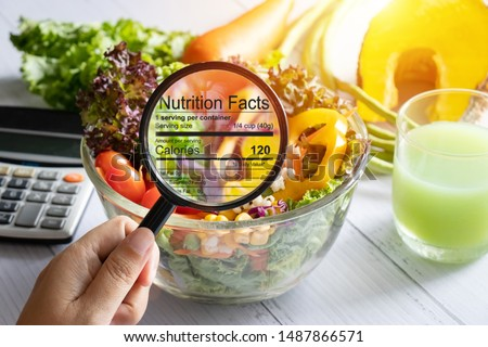 nutritional information concept. hand use the magnifying glass to zoom in to see the details of the nutrition facts from food , salad bowl #1487866571