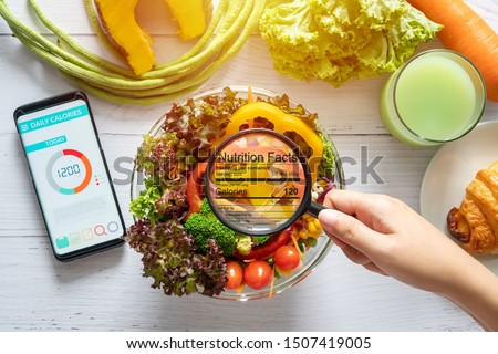 nutritional information concept. hand use the magnifying glass to zoom in to see the details of the nutrition facts from food , salad bowl #1507419005