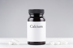 nutritional supplement calcium bottle and capsules on gray