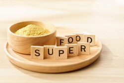 Nutritional yeast flakes in a bowl with wooden letters