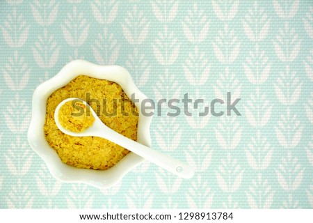 Nutritional yeast flakes in fluted white bowl and spoon on pale turquoise textured background shot from above. Horizontal format with room for text.