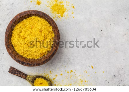 Nutritional yeast in a wooden bowl, copy space, white background, copy space. Healthy vegan food concept.