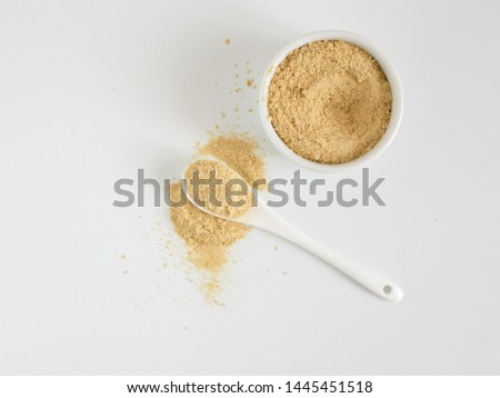 Nutritional yeast. Nutritional inactive yeast in small white ctramic bowl and white ceramic spoon. Copy space. Top view. Nutritional yeast is vegetarian superfood with cheese flavor, for healthy diet