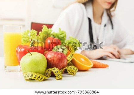 Nutritionist desk with healthy fruit, juice and measuring tape. Dietitian working on diet plan. Weight loss and right nutrition concept #793868884