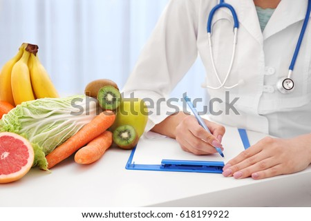 Nutritionist doctor writing diet plan on table #618199922