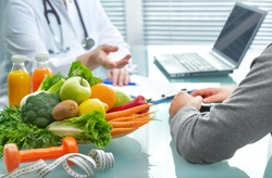 Nutritionist is consulting the patient about healthy diet with vegetables and fruits. Nutrition und dieting concept