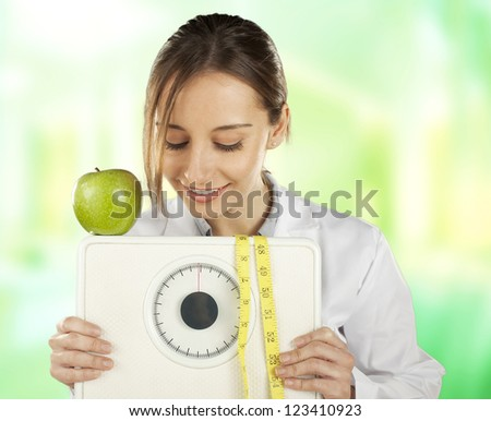 Nutritionist watching and holding a weight scale and green apple. Healthy eating and lifestyle concept