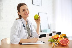 Nutritionist with apple and clipboard at desk in office