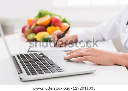 Nutritionist working on laptop and writing diet plan for patient, panorama, copy space