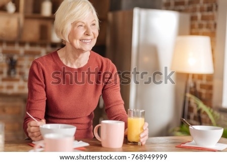 Nutritious breakfast. Upbeat senior woman sitting at the kitchen table, eating oatmeal and drinking orange juice while looking into the distance and smiling
