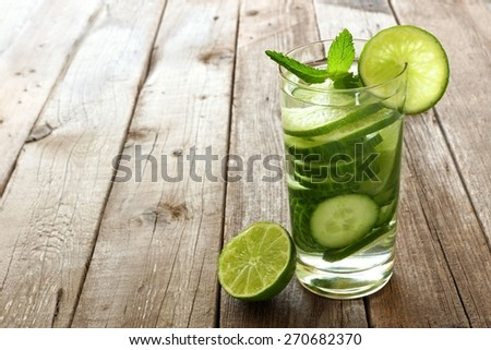 Nutritious detox water with lime and cucumber in a glass against a wood background