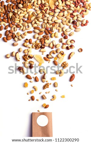 Nuts and dried fruits in the craft package. Photo for the catalog. Place for logo, your text. Assorted mixed nuts on white background. (walnut, brazil nut, pecan, pistachios, almond,  peanut, cashew
