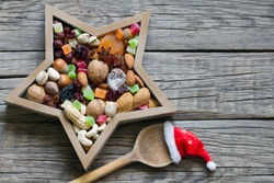 Nuts and dried fruits mix for Christmas with spoon and Santa's hat on wooden boards