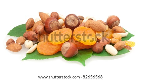 nuts and dried fruits on green leaves isolated on white background