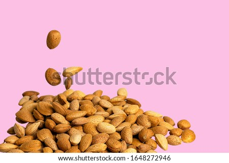 nuts are piled to a pile on a smooth pink background