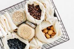 Nuts, dried fruits and  groats  in eco cotton bags and glass jars  in black metal basket. Zero Waste Food Shopping.  Waste-free living