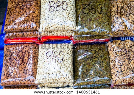 Nuts, dry fruits and pulses packed in clear plastic bags with prices ready for sale in an indian shop. These small packs offer a low cost purchase for indian households for a healthy snack and an