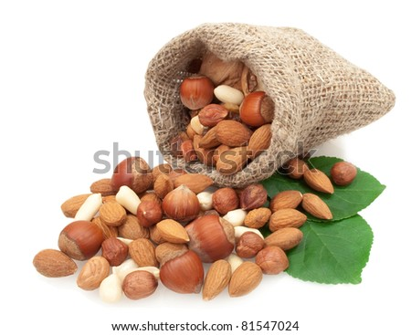 nuts in a linen basket on green leaves isolated on white background