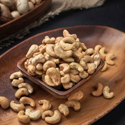 nuts on a square wooden bowl and an oval wooden tray on a dark background and burlap